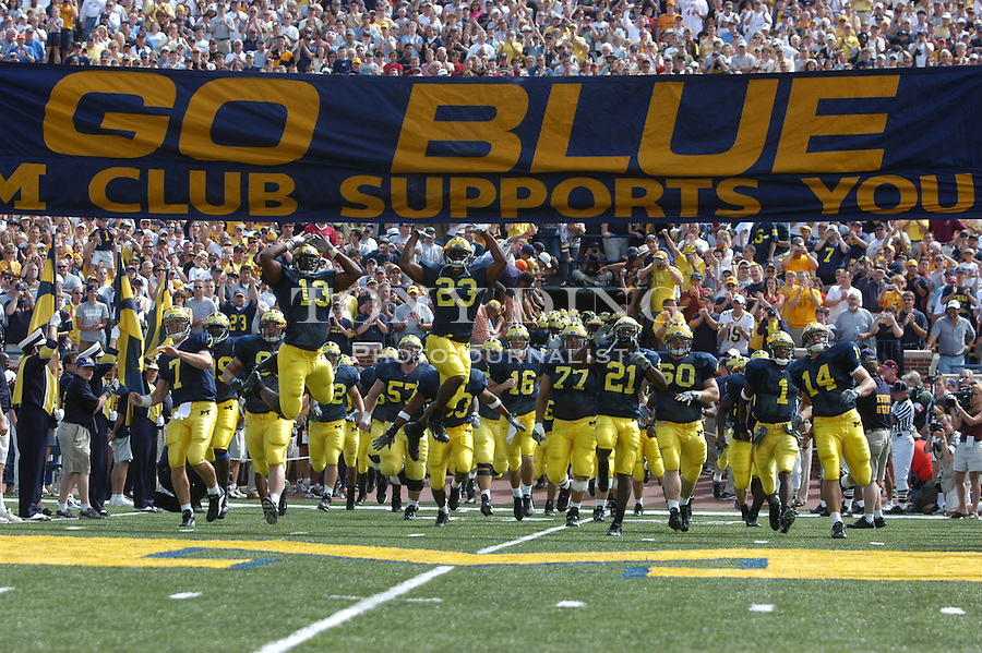 The Michigan football team storm the field before their 45-7 victory over Central Michigan at Michigan Stadium on Saturday, August 30, 2003 (TONY DING/Daily).