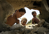 Elvis Palacios (12), Osbel Palacios (9) and Jesus Castillo through a wall were salvage rusty steel bars to sell from buildings flattened in 1999 by massive landslides in La Guaira, Vargas state near Caracas, 03 August, 2004. Child workers are an example of the poverty that is a constant reference in campaign speeches by President Hugo Chavez and his opponents as they head to a recall referendum on Aug. 15. REUTERS/Howard Yanes..FEATURE/PICTURE TAKEN 03 AUGUST, 2004