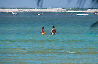 A young couple enjoying the ocean off Haena Beach Park, North Shore, Kauai.