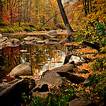 An October evening in Cherokee Park in Colby, Wisconsin.  The autumn foliage has recently been hit by fall winds and many of the leaves can be seen in the Big Eau Pleine River.