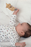 2 month old baby boy on back grasping toy vertical