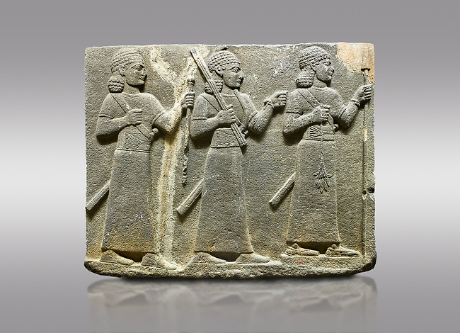 Picture & image of Hittite relief sculpted orthostat stone panel of Royal Buttress Basalt, Karkamıs, (Kargamıs), Carchemish (Karkemish), 900-700 B.C. Warriors. Anatolian Civilisations Museum, Ankara, Turkey.<br /> <br /> Three figures each with a long dress, a thick belt and curly hair. The figure in front holds a spear with a broken tip in his left hand and a leafy branch in his right hand. The figure in the middle made his left hand a fist, and he carries a tool with his right hand at the level of his head. They are followed with a figure holding a sceptre in his left hand. All three have each a long sword at their waist. <br /> <br /> Against a gray background.