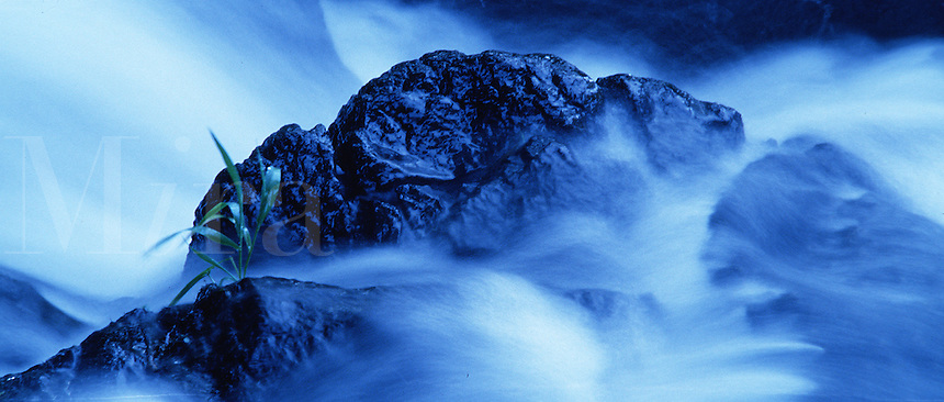 Blurred action image of a stream rushing over rocks.