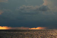 Sunset over the ocean obscured by heavy grey storm clouds, Maldives.