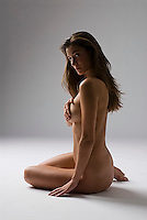 Nude woman sitting, hands over breast, side view