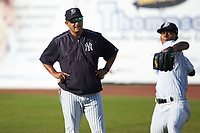 Pulaski Yankees pitching coach Gerardo Casadiego (55) watches starting pitcher Luis Medina (30) warms up in the outfield prior to the game against the Princeton Rays at Calfee Park on July 14, 2018 in Pulaski, Virginia. The Rays defeated the Yankees 13-1.  (Brian Westerholt/Four Seam Images)