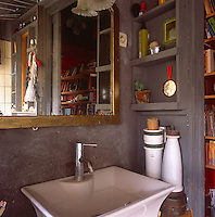 A detail of a grey painted bathroom. A gold framed mirror hangs above a washbasin.