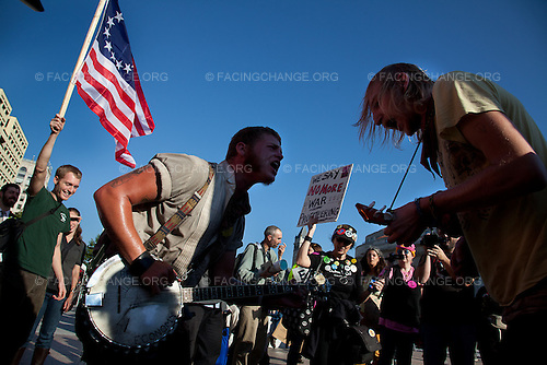 "Washington, DC.October 6, 2011..Banjo Youngblood (left) and Jamie Troutman (right) sang the lyrics, the revolution has just begun, to a boisterous crowd on Freedom Square during the first day of ""Occupy DC."""