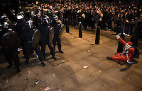A protestor dressed in a Santa Claus outfit sits on the ground as police approach during a student demonstration in Westminster, central London on the day the government passed a bill to increase university tuition fees.