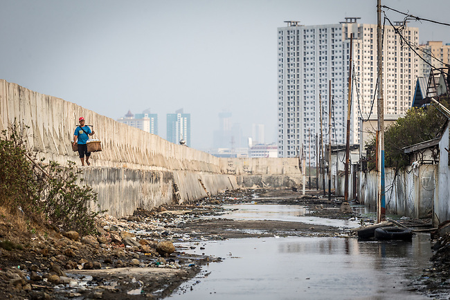 15 August 2019, Jakarta, Indonesia: A food seller walks beside the protective seawall barrier at Muara Baru, North Jakarta built by the Government to keep the ocean from encroaching through the sinking city. The city is sinking at such an alarming rate the Federal Government is planning to move the capital off the island of Java to alleviate some of the strain that is causing the city to sink so quickly such as the draining of the groundwater table. Picture by Graham Crouch/The Australian