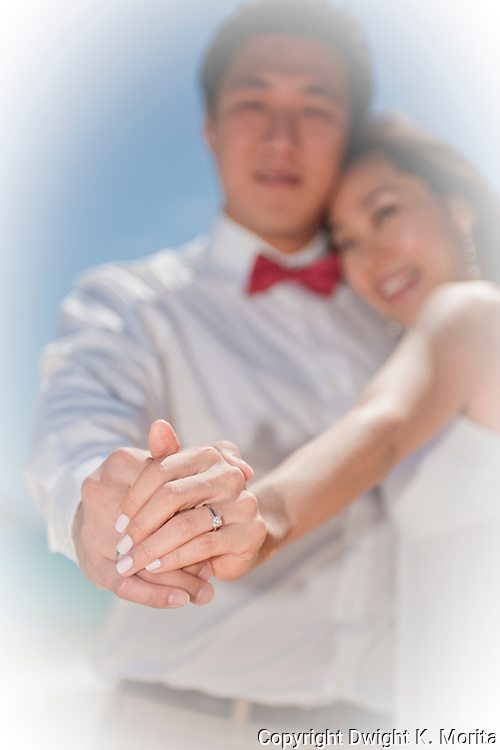 Asian bride and groom dance on Lanikai beach, showing off the wedding ring as they look forward to their life as a married couple following their wedding.