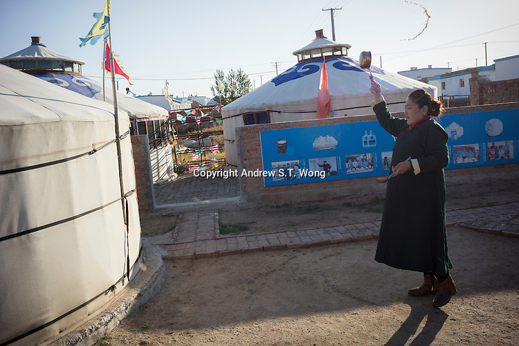 Mongolian Renqima splashes water during a daily rite to pay respects to heaven before breakfast at her dairy farm in Damao Banner, Inner Mongolia, China, October 2014.