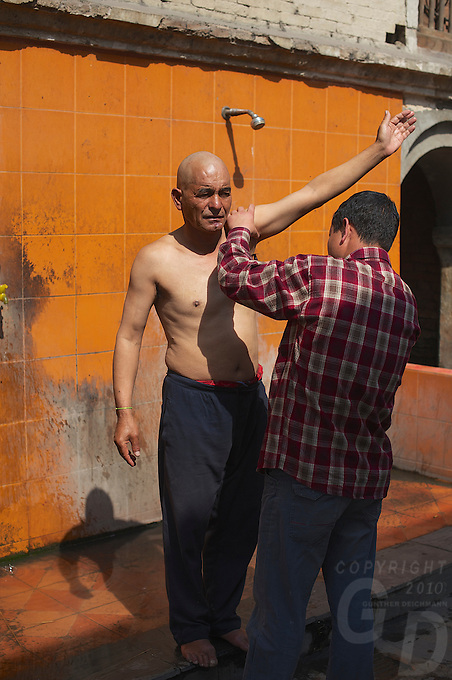 This man, the father his son died in an accident is getting all his body hair removed as part of the cremation ceremony at Pashupati Templs and cremation area Kathmandu, Nepal