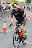 Pictured: Gareth Thomas cheers on as he rides past. Sunday 15 September 2019<br /> Re: Ironman triathlon event in Tenby, Wales, UK.