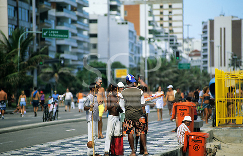 Rio de Janeiro, Brazil. Beach vendors; berimbau players and prawn kebab sellers on the road next to Ipanema Beach.