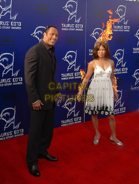 """DWAYNE """"THE ROCK"""" JOHNSON.at The 2007 Taurus Stunt Awards held at Paramount Studios in Hollywood, California, USA, May 20th 2007..full length brown suit girl with head hair on fire flames funny.CAP/DVS.©Debbie VanStory/Capital Pictures"""