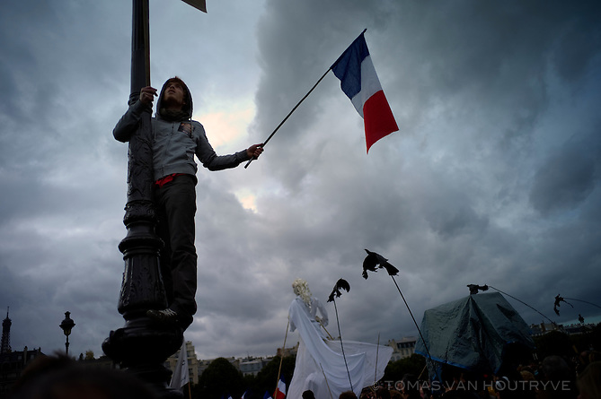 A protester waves a French flag while clinging to a pole at a demonstration at Les Invalides in Paris, France on Oct. 19, 2010. A proposal to reform pensions in France by raising the retirement age from 60 to 62 kicked off strikes and major protests against the Sarkozy government's austerity measures.