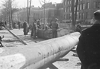 Photo from the NIOD's Huizinga collection. Tree trunks from the Haagse Bos, cut down for the construction of the Fortress Clingendael as part of the 'Atlantic Wall', are loaded in inland vessels on the Koningskade, The Hague. Menno Huizinga was part of the Hidden Camera and took pictures illegally during the occupation. He did this mainly in his hometown The Hague.