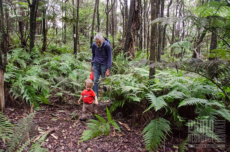 A local Caucasian man and a young boy hike along the native forest loop trail at Kalopa State Park, Hamakua Coast, Big Island.