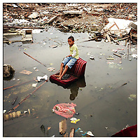 A child sits in a flooded district in central Jakarta, Indonesia. 40% of the city is below sea-level resulting in frequent flooding.