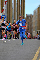 """3rd October 2021; London, England: The Virgin Money 2021 London Marathon: """"Dr CHRIS"""" (""""28049"""") dressed in medical outfit as the first fancy dress  running crosses Narrow Street Swing Bridge, Limehouse Basin between mile 14 and 15."""