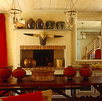 A long polished refectory table runs down the centre of the dining room and a collection of ceramics is displayed on an open shelf above the fireplace behind