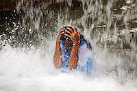 A young girl covers herself from falling water at Ancol Water Park in northern Jakarta.<br />
