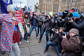 Photographers surround a young woman anti-Brexit protestor.  Brexit supporters demonstrate outside the Houses of Parliament as MPs vote on amendments to Theresa May's withdrawal deal with the EU.  Westminster, London.