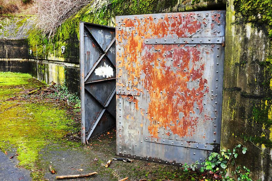 Open rusty steel door at concrete bunker tunnel, Artillery Hill, Fort Worden State Park, Port Townsend, Washington, USA