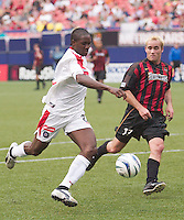 Chicago foward Damani Ralph shoots and scores while being marked by Joey DiGiamarino of the MetroStars. The Chicago Fire defeated the NY/NJ MetroStars 3-2 on 6/14/03 at Giant's Stadium, NJ..