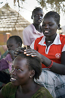 Young women from Panyok combing each others hair in their camp at the Twic Olympics in Wunrok, Southern Sudan.