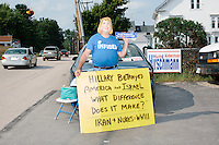Shalom International president Bob Kunst, of Miami, Florida, holds an anti-Hillary Clinton sign while wearing a halloween mask bearing her likeness outside the kick-off event at Texas senator and Republican presidential candidate Ted Cruz' s New Hampshire campaign headquarters in Manchester, New Hampshire.