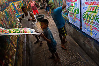 "Colombian sign painters take down just-finished music party posters in the sign painting workshop in Cartagena, Colombia, 12 December 2017. Hidden in the dark, narrow alleys of Bazurto market, a group of dozen young men gathered around José Corredor (""Runner""), the master painter, produce every day hundreds of hand-painted posters. Although the vast majority of the production is designed for a cheap visual promotion of popular Champeta music parties, held every weekend around the city, Runner and his apprentices also create other graphic design artworks, based on brush lettering technique. Using simple brushes and bright paints, the artisanal workshop keeps the traditional sign painting art alive."