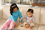 16 month old toddler boy playing toy musical instrument xylophone assisted by sister age 8 horizontal