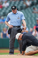 Home plate umpire Joseph Born supervises as repairs are made to the pitching mound prior to the game between the Pawtucket Red Sox and the \ck at BB&T Ballpark on August 8, 2014 in Charlotte, North Carolina.  The Red Sox defeated the Knights  11-8.  (Brian Westerholt/Four Seam Images)