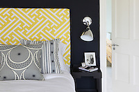 Detail of a yellow and white geometrically patterned headboard with contrasting grey cushions