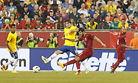 Portugal forward Nelson Oliveira (9) passes the ball as Brazil defender Maxwell (14) defends. In an international friendly, Brazil (yellow/blue) defeated Portugal (red), 3-1, at Gillette Stadium on September 10, 2013.