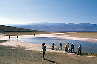 Death Valley National Park, California, CA, USA - Tourists walking on Salt Flats at Badwater Basin, Panamint Mountains in Distance