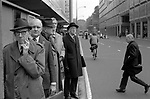 Office workers commuters queue at a bus stop waiting for a bus. 1970s 1976 London UK