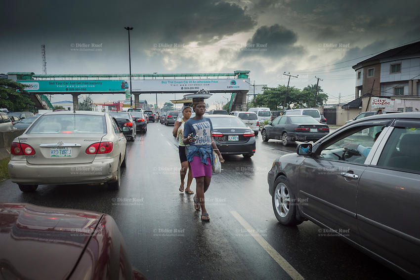 """Nigeria. Lagos. Traffic jam on the late afternoon. Street vendors. Two women walk in between cars and carry on their heads a tray with goods to sell. On the pedestrian overpass, various billboards with advertisings, such as """" Sell you car and get paid instantly"""" ,"""" Buy that dream car at an affordable price"""". Lagos is a city in the Nigerian state of the same name. The city, with its adjoining conurbation, is the most populous in Nigeria and on the African continent. It is one of the fastest growing cities in the world and one of the most populous urban areas. 26.06.19 © 2019 Didier Ruef"""