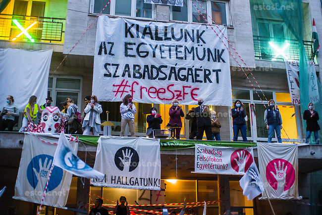 UNGARN, 27.09.2020, Budapest VIII. Bezirk. Im Zeichen des konservativ-autoritaeren Kulturkampfes uebernehmen regierungsnahe Kreise die Theater- und Filmhochschule SzFE. Die Studenten reagieren am 31.08 mit der Besetzung und der Blockade des Gebaeudes. -Demonstration fuer die Autonomie der Universitaeten. Die StudentInnen fuehren einen bedrohlichen Drachen mit sich. links sein abgeschlagener Kopf. Vor der Uni in der Vas utca. | As part of the conservative-authoritarian Kulturkampf circles close to the government take control of the University of Theatre and Film Arts SzFE. On Aug. 31 the students react by occupying and blocking the building. -Demonstration for the universities' autonomy. Students employ a big dragon, its cut-off head is seen to the left. In front of the university in Vas street. <br /> © Martin Fejer/estost.net