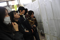People look at evacuation lists in the town of Natori, hoping to see the names of missing relatives.  The Tsunami devastated ahe entire pacifc coastline of Japan after the earthquake and tsunami devastated the area Sendai, Japan.<br />