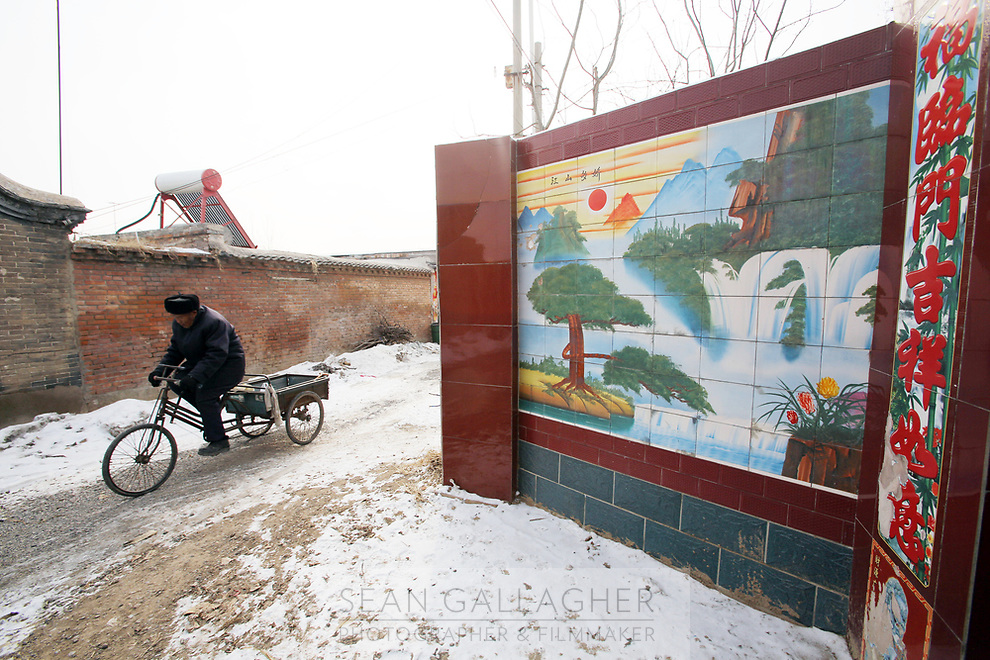 A villager cycles past an elaborate and newly built wall in Dongzhuangying Village, on the southern outskirts of Beijing. Villagers have been building new extensions to their properties in-light of news that their village will be destroyed to make way for a new city airport. Villagers will be compensated more depending on the area of their homes, resulting in new buildings appearing across the village, as villagers anticipate higher amounts of compensation from local government. China. Friday 25th January, 2013.