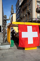 Switzerland. Canton Ticino. Chiasso. A giant swiss flag on a small shop on a market day. Sculptures in the street. 08.04.11 © 2011 Didier Ruef