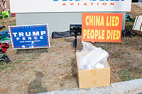 """A Trump/Pence campaign sign stands next to a sign reading """"China Lied / People Died"""" outside a Make America Great Again Victory Rally with US President Donald Trump in the final week before the Nov. 3 election at Pro Star Aviation in Londonderry, New Hampshire, on Sun., Oct. 25, 2020. The sign on the right is a reference to China's role in the ongoing Coronavirus (COVID-19) global pandemic."""
