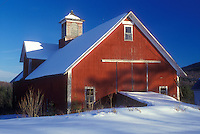 Vermont, VT, Red barn in the snow in winter in Ryegate.