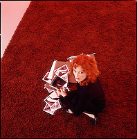 Red haired woman holding files and photos looking at camera<br />