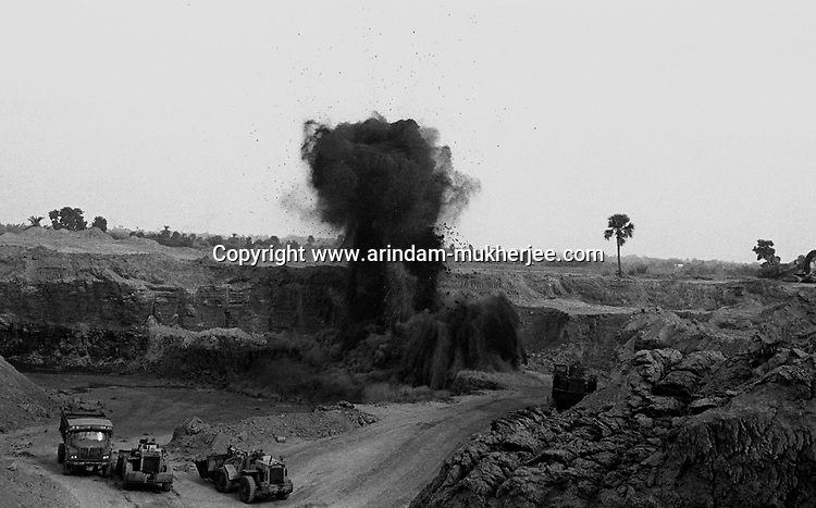 An explosion ids made in an open cast pit. This explosions are major reasons for ecological disbalance in these areas. Open cast mining is the modern form of mining. North Searsole Coliery in Ranigunj, West Bengal, India. Arindam Mukherjee