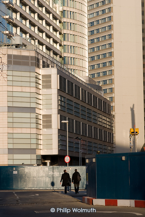 Two pedestrians walk past the back of the Hilton London Metropole hotel and a construction site at Paddington Basin