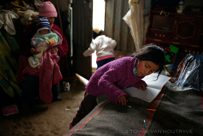 Maria de los Angeles Oscanoa Huaman does her homework on the bed at home in the Paragsha neighborhood of Cerro de Pasco, Peru. Three of the Oscanoa children tested with extremely high levels of lead in their blood, including Maricielo Cardenas Huaman, 11 years old, 22.90%, Maria de los Angeles Oscanoa Huaman, 5 years old, 29.56%, and Brayan Oscanoa Huaman, 3 years old, 31.99%.